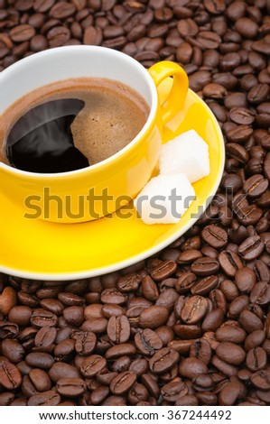 Yellow coffee cup and saucer with freshly brewed coffee on a base of coffee beans; Black and aromatic pick-me-up - stock photo