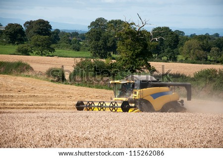 Yellow combine harvester working in a field - stock photo