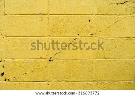 Yellow concrete brick wall texture - stock photo