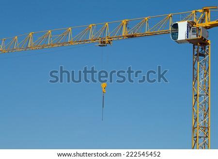 Yellow construction crane, blue cloudless sky - stock photo