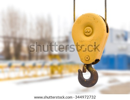 Yellow construction crane hook with some industrial buildings on the background - stock photo