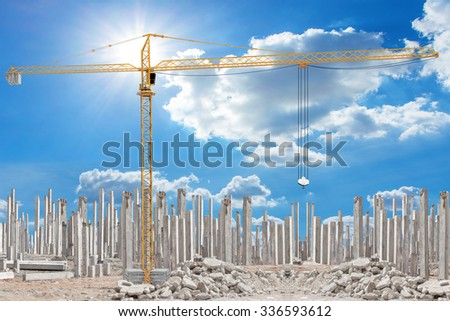 Yellow construction crane tower working at building under construction with precast concrete piles - stock photo