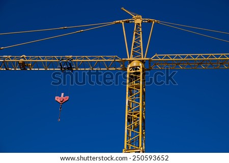 Yellow construction crane with pulley - stock photo