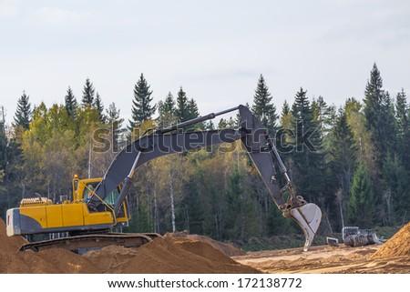 Yellow Construction Excavator at Work - stock photo