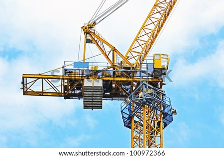 Yellow construction tower crane against blue sky - stock photo