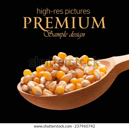 Yellow corn in a wooden spoon / kernels on wooden spoon isolated on black background with place for your text  - stock photo