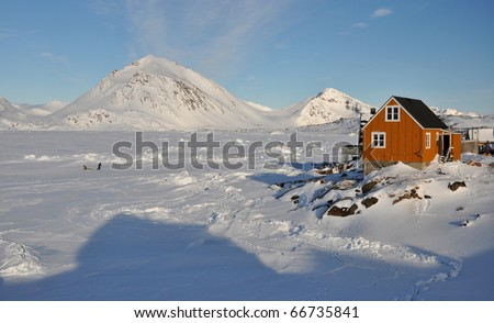 Yellow Cottage in the Kulusuk village and seal hunter, Greenland - stock photo