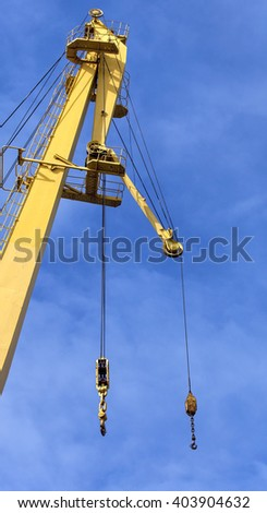 yellow crane hook against the blue sky - stock photo