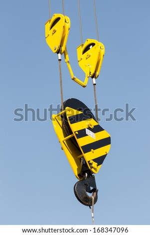 Yellow crane hook on a blue sky - stock photo
