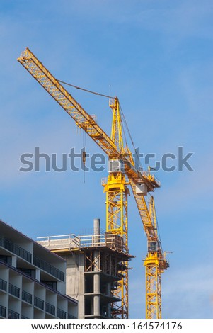 Yellow crane working on a construction site - stock photo