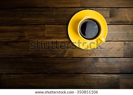 yellow cup coffee on wood background - stock photo
