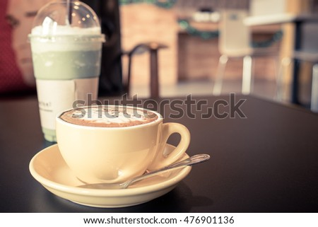 yellow cup of coffee on cafe table with green tea smoothie