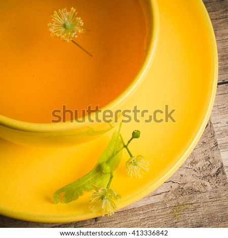 Yellow cup with linden tea on the table,  top view - stock photo