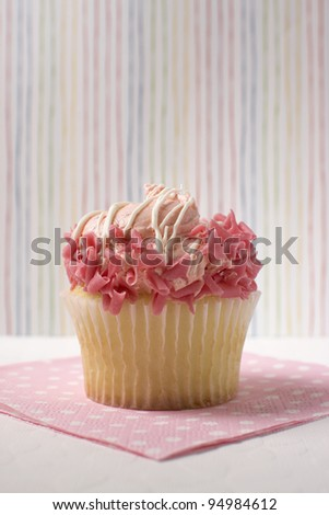Yellow cupcake decorated with pink icing against a multi-colored striped background. - stock photo
