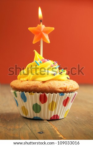 Yellow cupcake with star birthday candle on a wooden table - stock photo