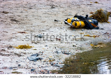 Yellow cylinders lying on sandy coast for diving