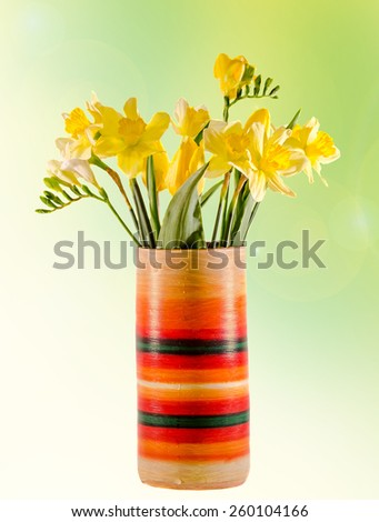 Yellow daffodils and freesias flowers in a vivid colored vase, close up, isolated, green to yellow degradee background. - stock photo