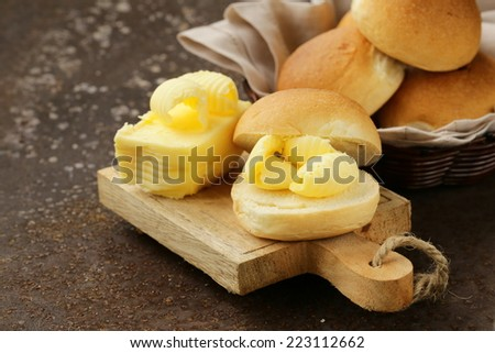 yellow dairy butter on a fresh bun bread for breakfast - stock photo