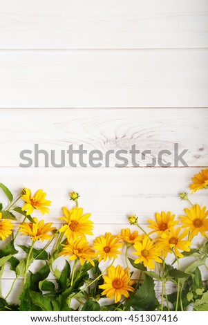 Yellow daisy flowers on light wooden background. High top view.