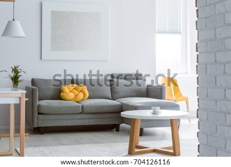 living room coffee table. Yellow decorative pillow on grey sofa in living room with brick white wall  and simple coffee Coffee Table Stock Images Royalty Free Vectors