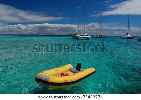 Yellow dinghy with catamarans on turquoise water of Gabriel Island lagoon - stock photo