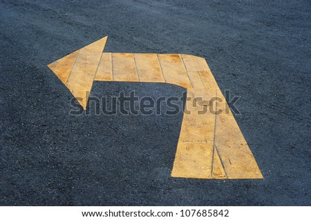 Yellow Directional Arrow on Asphalt
