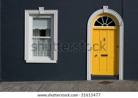 yellow door, white windows, black wall - stock photo