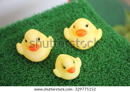 yellow duck toy on green garden