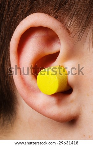 yellow earplug into the ear close up - stock photo