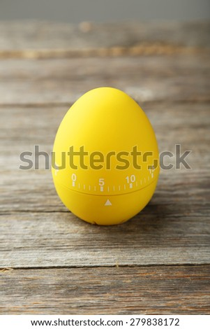 Yellow egg timer on grey wooden background - stock photo