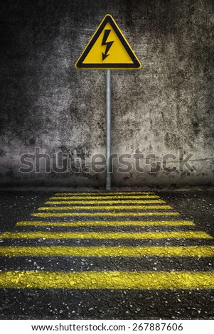 yellow electricity warning sign at grunge wall in front of pedestrian crossing  - stock photo
