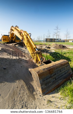 yellow excavator at construction site digging sand - stock photo