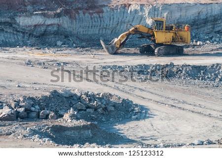 Yellow excavator loader lignite. Work in the mine. - stock photo