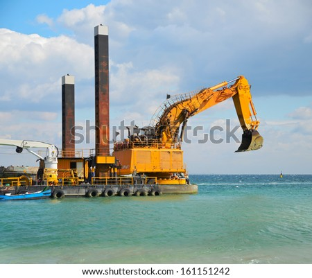 Yellow excavator machine construct sea defences on the beach - stock photo