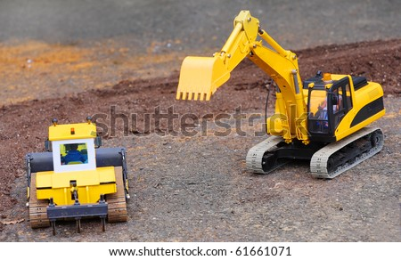 Yellow excavator on a road building. Homemade RC model - plastic kit ( scratchbuild 1 : 32 scale) - stock photo