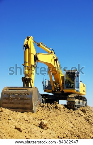 Yellow excavator on a working platform - stock photo