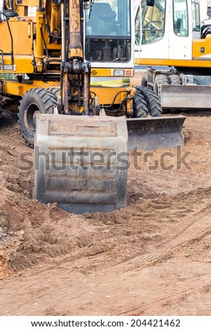 Yellow excavator on new road construction site - stock photo