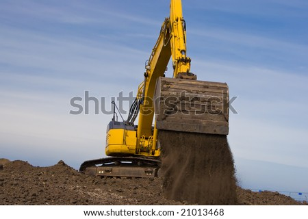 Yellow excavator unloading dirt against a blue sky. - stock photo