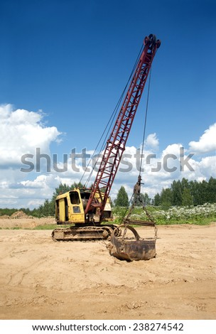 Yellow excavator with big heavy bucket standing on sand on background of forest and clear blue sky on a summer day vertical view - stock photo