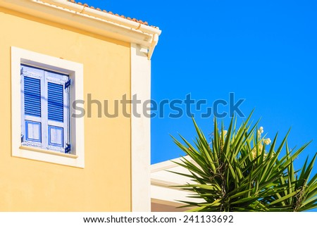 Yellow facade of typical Greek house in Fiskardo town, Kefalonia island, Greece - stock photo