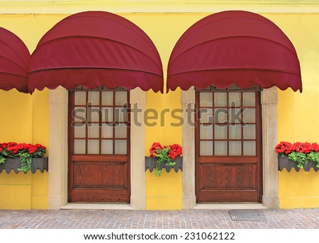yellow facade with two entrances, nostalgic red marquee, italy - stock photo