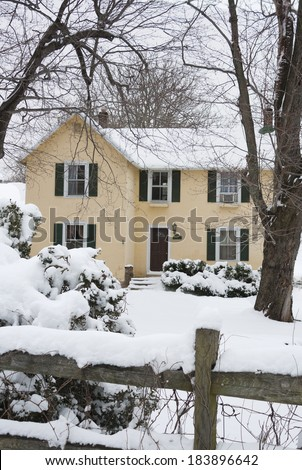 Yellow farmhouse with green shutters in the snow in Warrenton, Virginia. Bare trees and fence post are in the in the foreground. - stock photo