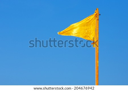 Yellow flag against the background of clear blue sky - stock photo