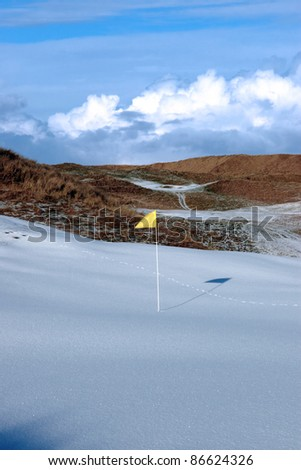 yellow flag on a snow covered links golf course in ireland in winter - stock photo