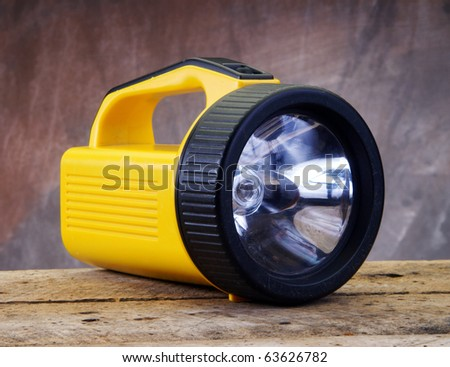 Yellow Flash Light on wood table top - stock photo