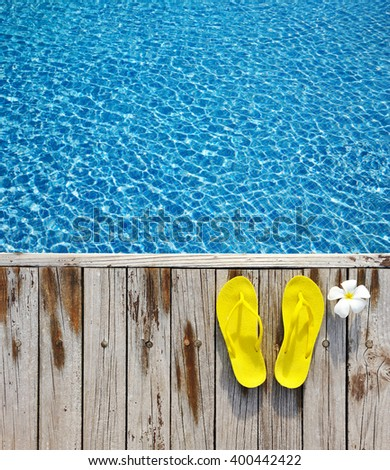 Yellow flip-flops by a swimming pool  - stock photo