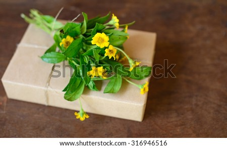 yellow flower bouquet on handcraft gift boxes over wooden table.  - stock photo