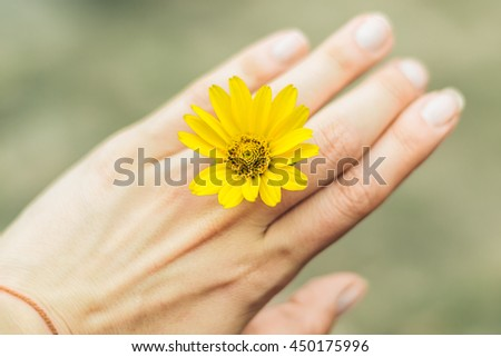 Yellow flower on a finger ring