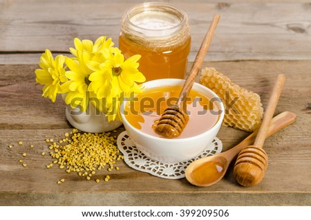 Yellow flowers and bee products (honey, pollen, honeycombs) on wooden background - stock photo