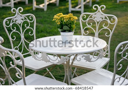 Yellow flowers in a bucket on a white table in the garden. Metal Garden Furniture Stock Images  Royalty Free Images   Vectors